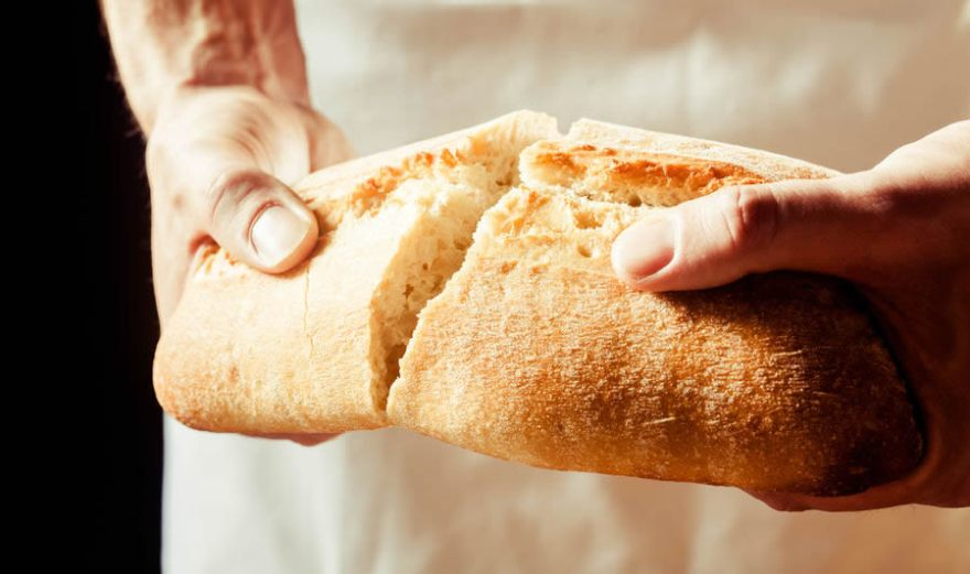 hands breaking a loaf of bread